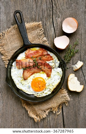 Fried eggs with bacon in frying pan on wooden background, top view - stock photo