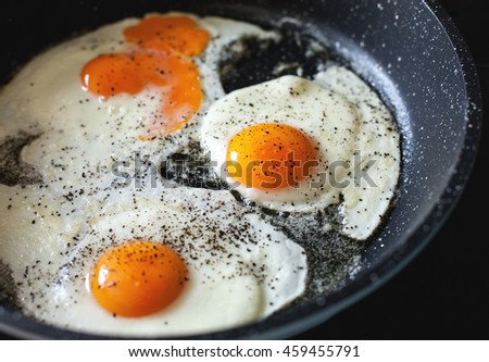 Fried eggs with black pepper in a frying pan - stock photo