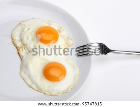fried eggs with fork - stock photo