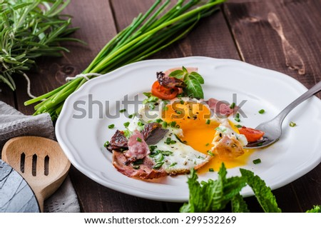 Fried eggs with ham and herbs, mini tomatoes and lots of herbs