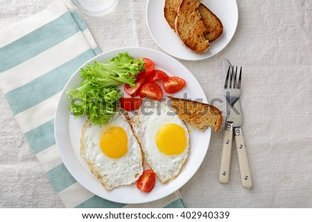 Fried Eggs with lettuce, tomato and bread. Top view