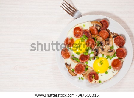 fried eggs with mushrooms and sausage - stock photo