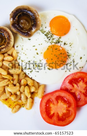 Fried eggs with mushrooms, beans and tomato served for breakfast