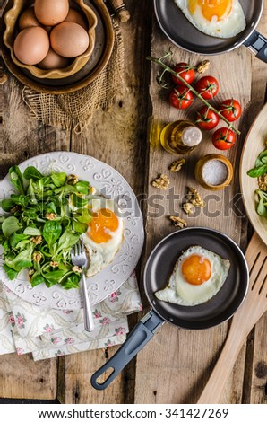 Fried eggs with salad and nuts, rustic photo - stock photo
