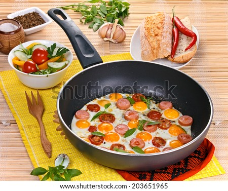 Fried eggs with sausage and tomatoes  in  frying pan  served with salad and bread. - stock photo