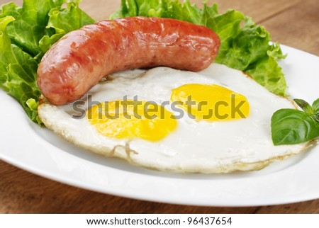 Fried eggs with sausage lettuce and basil