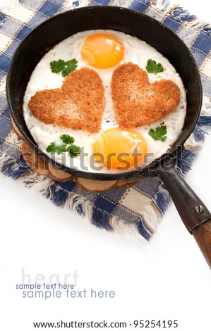 fried eggs with slices of bread in the shape of a heart in the frying pan - stock photo