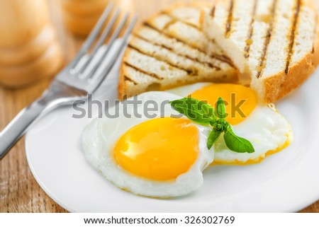 Fried eggs with toasts - stock photo