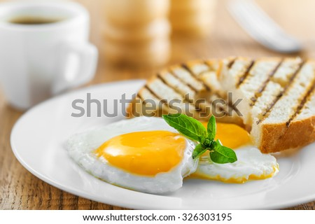 Fried eggs with toasts and coffee, traditional breakfast - stock photo