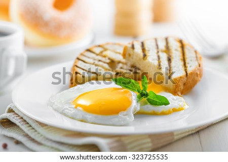 Fried eggs with toasts, coffee and donuts, traditional breakfast, close-up