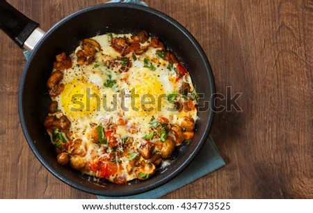 fried eggs with vegetables, mushrooms and cheese in a frying pan on wooden table - stock photo