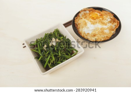 Fried fern vegetable and rice with crispy fried egg with space on wood table horizontal style - stock photo