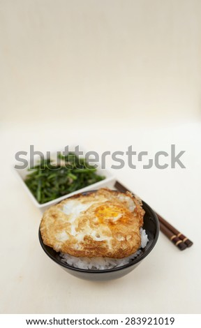 Fried fern vegetable and rice with crispy fried egg with space on wood table vertical style - stock photo