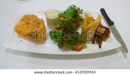 Fried fish and chicken steak , salad , french fries - stock photo