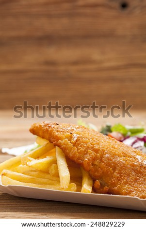 Fried fish and chips on a paper tray - Natural wooden background - stock photo