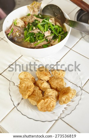 Fried fish cake and fish soup on the table - stock photo