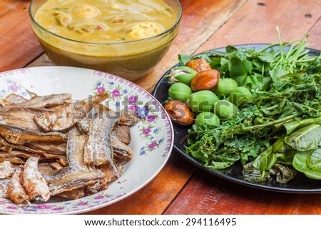 Fried fish ,curry egg with coconut milk and fresh vegetable in plate on wooden table