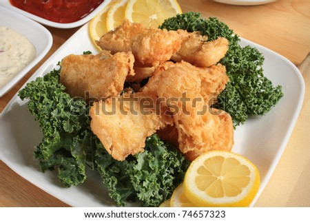 fried fish dish close-up with sauce and lemon - stock photo