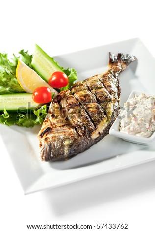 Fried Fish (Dorado) Garnished with Lemon, Tomato, Cucumber and Sauce - stock photo