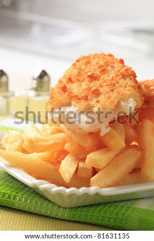 Fried fish fillet and heap of French fries - stock photo