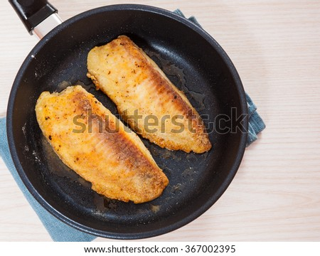 Fried fish fillet in a frying pan