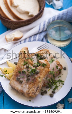 Fried fish fillet with butter sauce and capers - stock photo