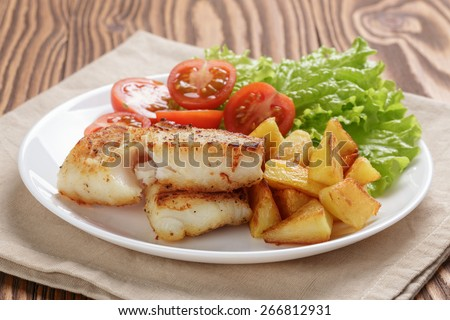 fried fish fillet with vegetables on wood table - stock photo