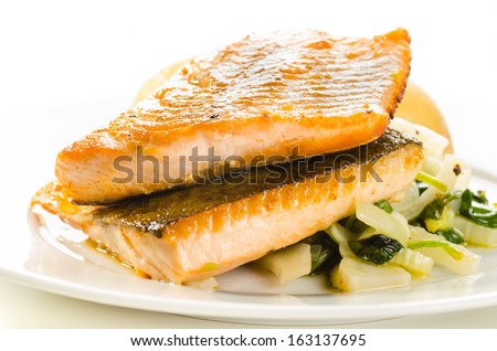 Fried fish fillets with vegetable garnish on white - stock photo
