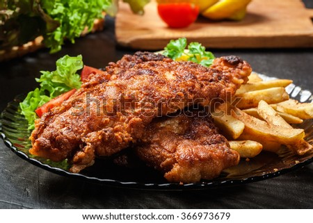 Fried fish in crispy batter with chips on a plate - stock photo