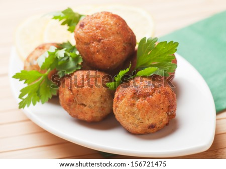 Fried fish meatballs with lemon and parsley - stock photo