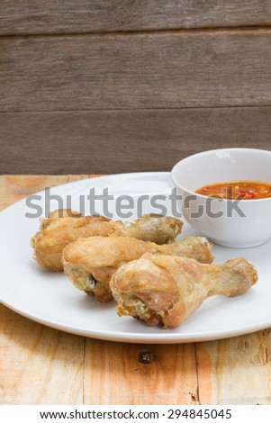 Fried fish sauce marinated chicken drumstick and sauce on white plate. - stock photo