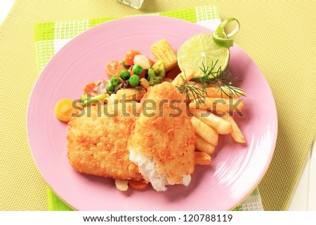 Fried fish served with French fries and mixed vegetables  - stock photo
