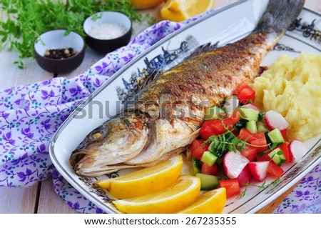 Fried fish served with mashed potato, lemon slice and vegetables salad - stock photo