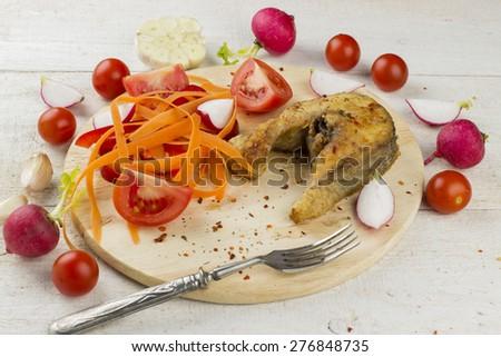 fried fish with carrots, tomato, garlic, garden radish - stock photo