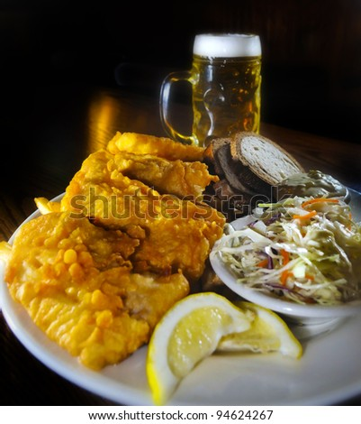 Fried Fish with coleslaw bread and tartar sauce, glass of beer in the back - stock photo