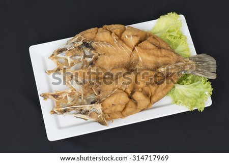 fried fish with fresh herbs and sweet spicy sauce on plate in black background