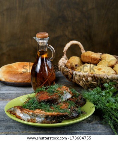 Fried fish with greens and olive oil - stock photo