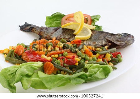 Fried fish with vegetables and lemons - stock photo