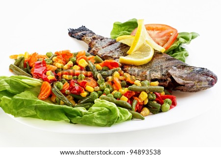 Fried fish with vegetables and lemons. - stock photo
