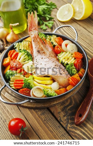 Fried fish with vegetables in the  frying pan - stock photo