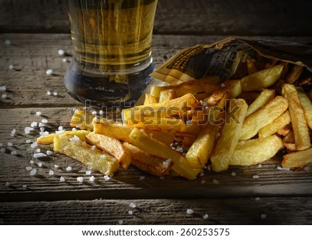 fried french fries and beer on a wooden background - stock photo
