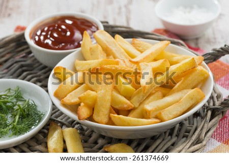 fried french fries with tomato sauce and herbs, close-up - stock photo