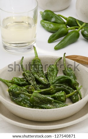 Fried green peppers in salt. Pimientos del Padron. White background. Spanish Cuisine.