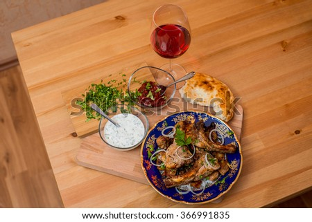 Fried grilled meat served with bread, sauces and wine - stock photo