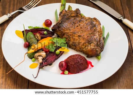 Fried Grilled pork steak on the bone with vegetables, mashed beetroot and berry sauce. Wooden background. Close-up