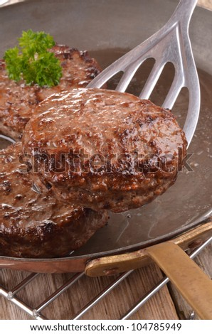 fried hamburger meat in a hot copper pan - stock photo