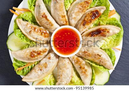 Fried Jiaozi with chilli sauce and salad - stock photo