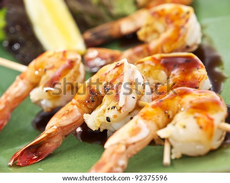 Fried kebab of shrimps with vegetables and sauce - stock photo