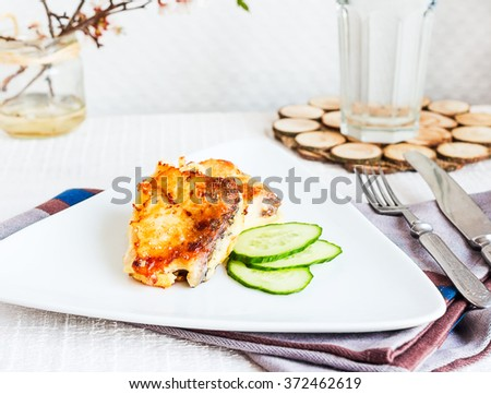 fried mackerel, fish in batter with a fresh cucumber on a light background