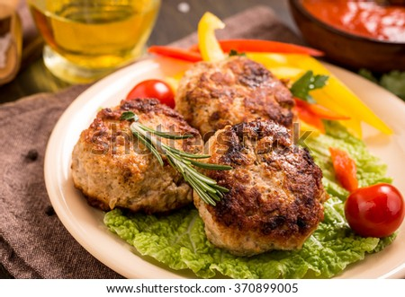 Fried meat cutlets with vegetables on plate. Closeup